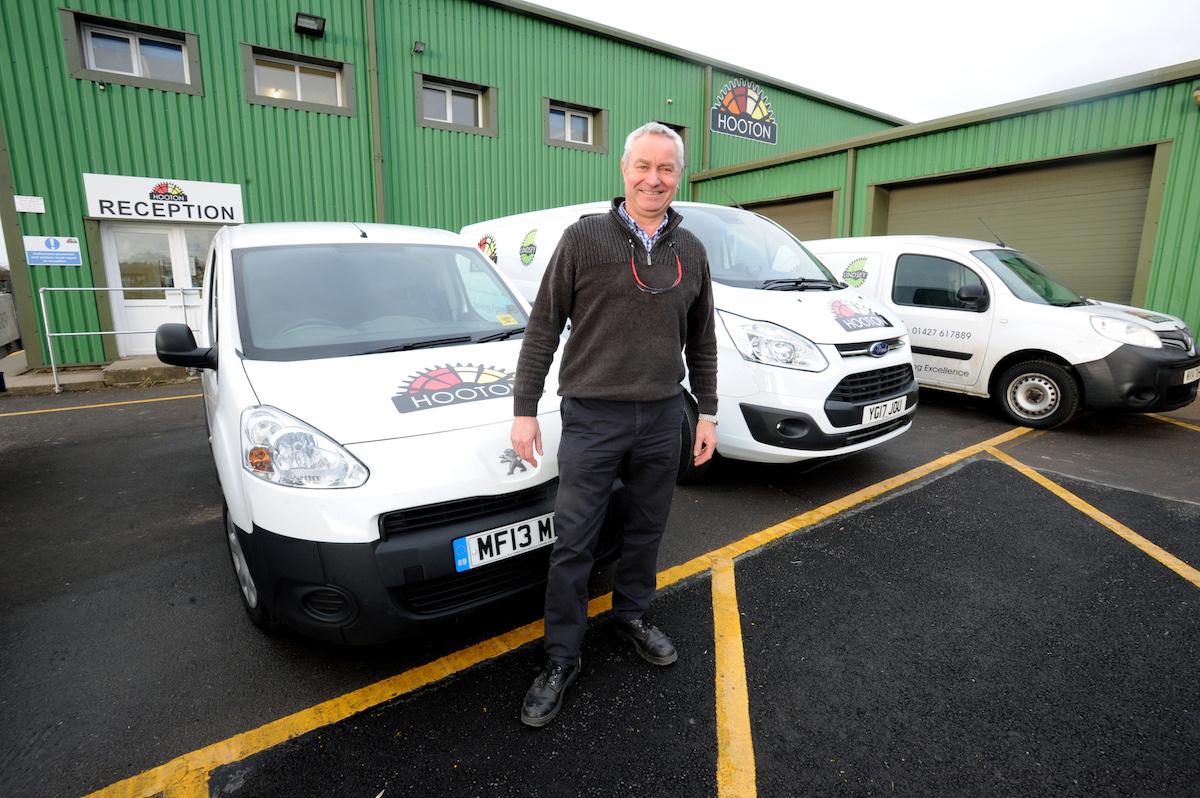 Man stood outside a work environment reception in front of 3 branded vans