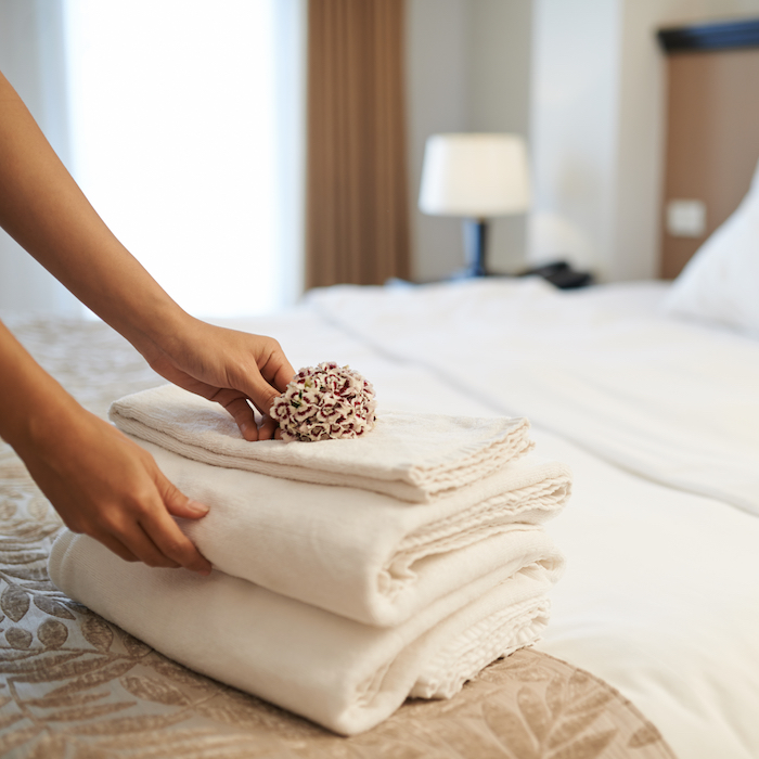 Hands placing a tower of 3 towels and a flower on a made bed in a hotel room