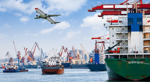 Port image featuring cranes, large ships and an aeroplane overhead