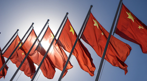 6 Chinese flags against a clear blue sky