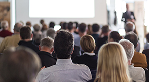 Large group of people sat down at an event listening to a presentation