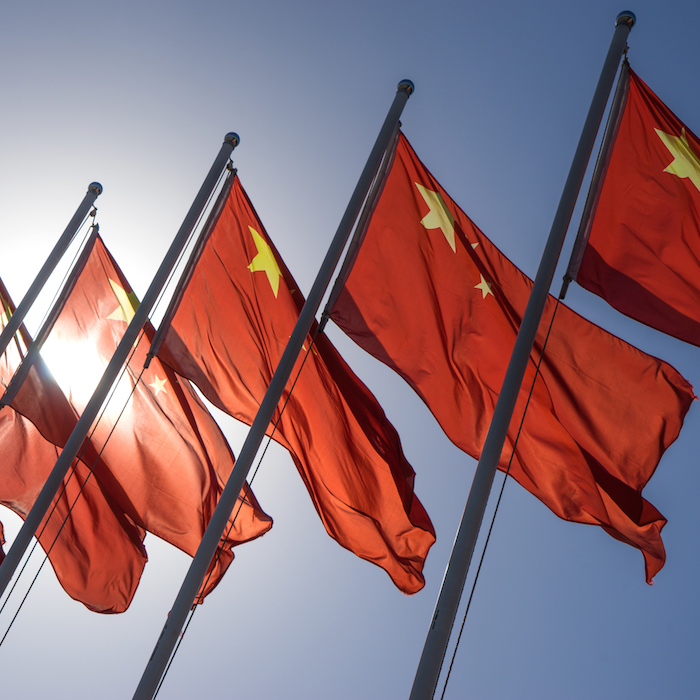 Row of Chinese flags against a blue sky