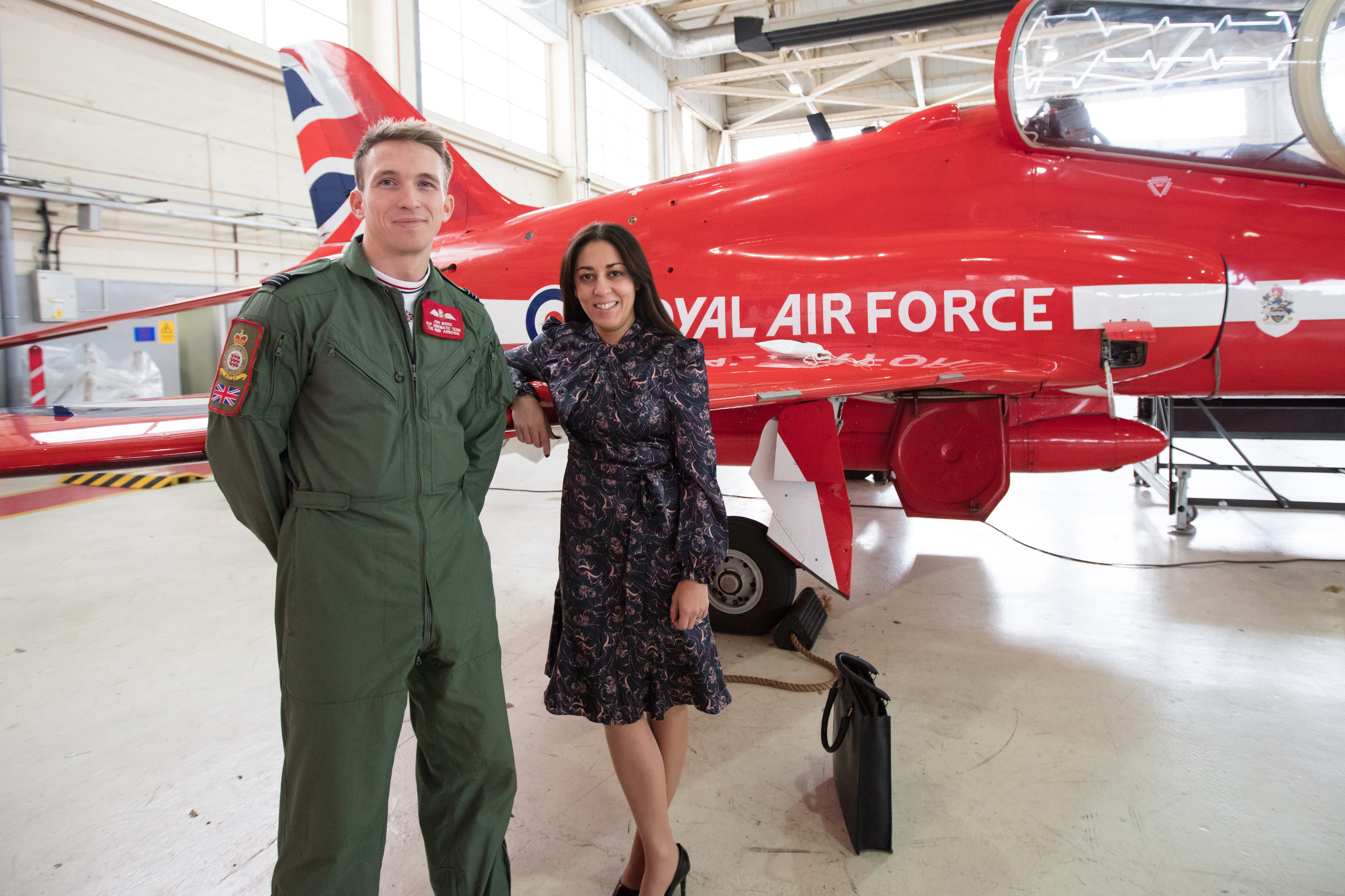Lady stood next to gentleman in green flight suit with a RAF Red Arrow aeroplane in the background