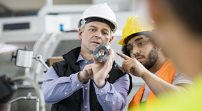 2 people wearing PPE working in a manufacturing environment