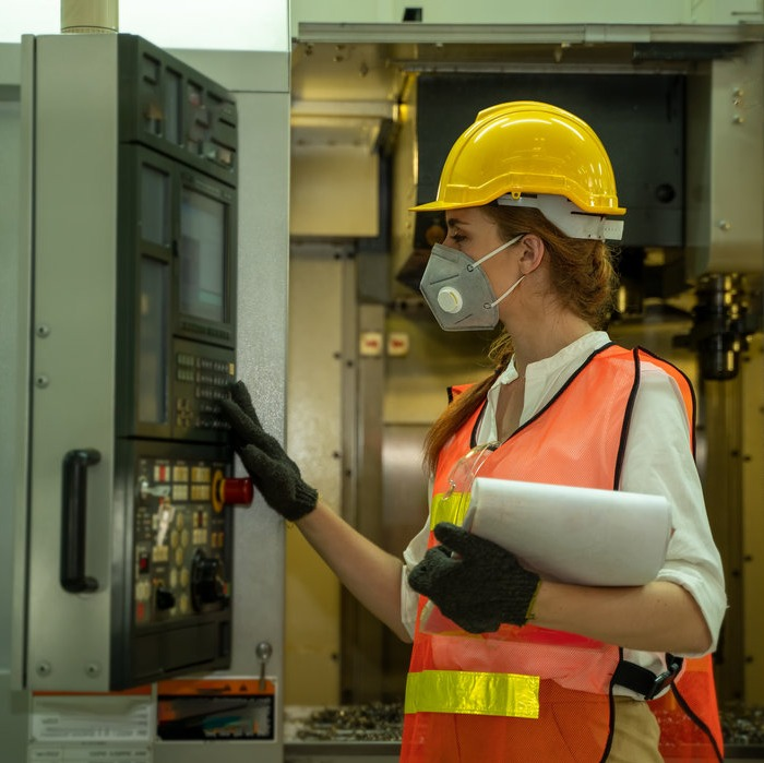 Women in construction work gear using manufacturing equipment